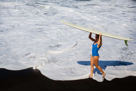 Sporty girl in bikini with surf board walk on black sand beach. Young surfer woman run by water pool with white foam. Active people in sports adventure camp, extreme activity on summer family vacation