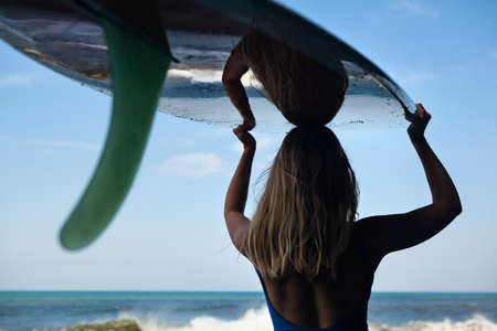 Girl in bikini with surfboard walk on black sand beach. Surfer woman look at sea surf and water pool with white foam. Active people in sport adventure camp, extreme activity on summer family vacation 写真素材