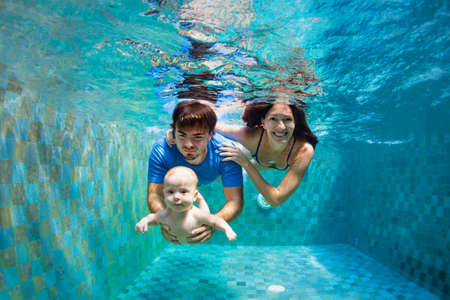 Happy family - mother, father, baby son learn to swim, training to dive underwater with fun in swimming pool to keep fit. Healthy lifestyle, active parent, people water sport activity, swimming lesson