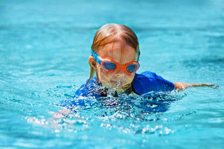 Happy child in wetsuit and goggles learn to swim, have fun in outdoor pool. Healthy family lifestyle, little kids water sports activity, swimming lessons with parents at training aqua classes. Imagens