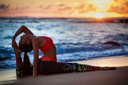 Sunset meditation. Young active woman stretching in yoga pose on sea beach to keep fit and health. Healthy lifestyle, flexibility training, sport activity in sport camp on summer family holiday. 版權商用圖片
