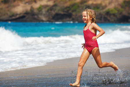 Happy barefoot child have fun on beach walk. Girl run along sea surf by water pool and jump with splashes. Family travel lifestyle, swimming activities. Summer vacation with kids on tropical island