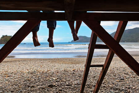 Happy kids have fun on beach walk. Children sit on lifeguard tower edge, dangling bare feet, look at sea surf. Black silhouette. Vacations travel lifestyle, outdoor activities in family summer camp.