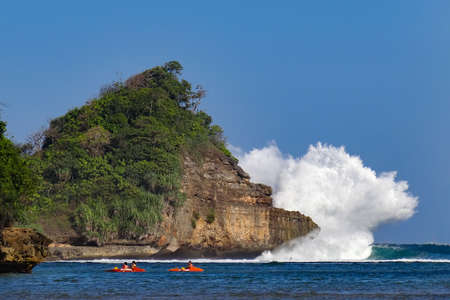 People paddling on kayak in flatware lagoon. On background huge ocean waves break with high splashes by cliff. Travel lifestyle, recreational water activity and watersport on summer sea beach vacation 스톡 콘텐츠