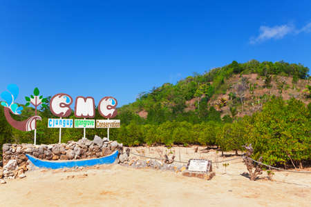Clungup beach, Indonesia - July 08, 2018: Clungup mangrove conservation signboard. Jungle walking trail among mangrove trees in ocean tidal ecosystem. Popular travel destination in Java island.