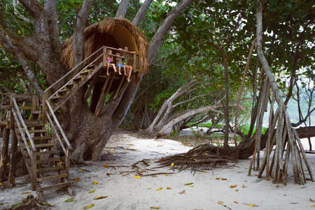 Happy children have fun on beach walk. Kids, young mother sit on balcony edge of tree house dangling legs, look at sea through jungle. Vacation lifestyle, outdoor travel activity in family summer camp