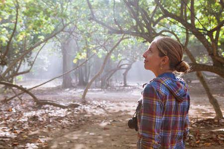 In de mistige ochtend loopt het gelukkige meisje met fotocamera alleen over het junglepad, verken het tropisch regenwoud. Familie reizen levensstijl, outdoor wandelactiviteit. Zomervakantie met kind op tropisch eiland
