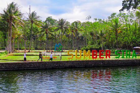 Malang, Indonesia - July 11, 2018: Kids walking on background of Sumber Sira sign - spring water spa with natural swimming pool. Popular place for family holidays day tour. Travel destination in Java