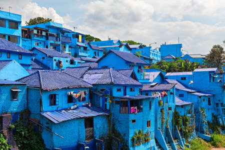 Panoramic view of village with old houses painted in blue color. Popular place to visit for city tour on family holidays. Travel destination in Malang, East Java, Indonesia