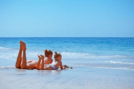 Happy family lifestyle at beach sea surf. Little child, young mother in bikini relaxing on white sand in water pool. Swimming activities on tropical island holiday with kids. Summer travel banner.