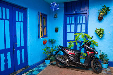 Malang, Indonesia - July 12, 2018: Motorbike parked in front of door on street of blue houses village Kampung Biru Arema. Popular place to visit for city walking tour. Travel destination in East Java