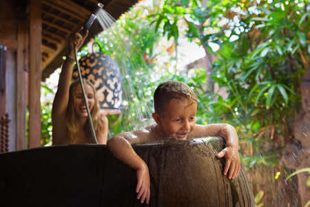 Happy baby son with mother have fun in bath. Playful woman spraying child from shower in outside bathroom on open veranda with beautiful tropical garden view in luxury villa on summer family vacation. 版權商用圖片