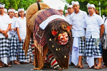 Bali, Indonesia - June 23, 2018: Dancer men in ethnic costumes walk with traditional mask of Balinese good spirit Barong on hindu ceremony Ngelawang during temple festival.