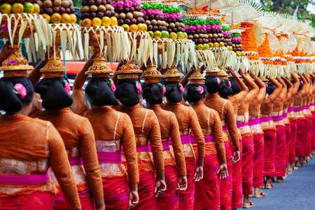 Gruppo di belle donne balinesi in costume - sarong, portano l'offerta per la cerimonia indù. Danze tradizionali, festival artistici, cultura dell'isola di Bali e del popolo indonesiano. Sfondo di viaggio indonesiano