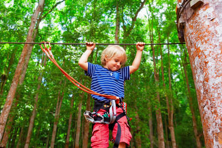 Child in safety harness, protective strips fastened by carabiners to wire. Climb on tree top, pass hanging bridge in adventure rope park. Outdoor activity, family lifestyle in summer camp on vacation Stock Photo