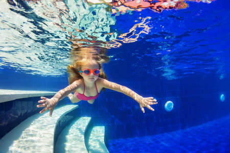 Happy family in swimming pool. Smiling child in goggles swim, dive in pool with fun - jump deep down underwater. Healthy lifestyle, people water sport activity, swimming lessons on holidays with kids Stock Photo - 111003765