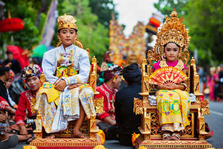 Denpasar, Bali island, Indonesia - June 23, 2018: Beautiful young children in traditional Balinese royal family dance costumes with golden headdress on street parade at art and culture festival.