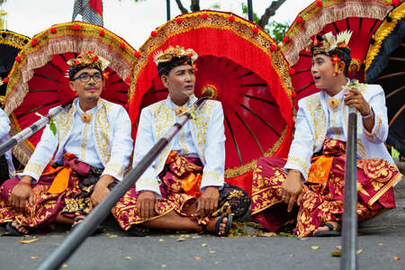 Bali, Indonesia - June 23, 2018: Group of young dancer men in ethnic costumes with traditional red, black and yellow umbrellas on hindu ceremony parade during temple festival. Balinese people culture. Stock Photo - 111646510