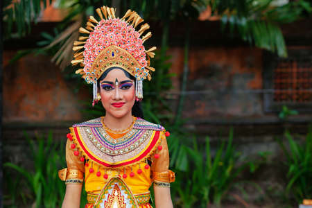 Denpasar, Bali island, Indonesia - June 23, 2018: Face portrait of beautiful young woman in traditional Balinese dance costume with golden headdress on street parade at art and culture festival. Stock Photo - 111646511