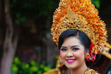 Denpasar, Bali island, Indonesia - June 23, 2018: Face portrait of beautiful young woman in traditional Balinese dance costume with golden headdress on street parade at art and culture festival. Stock Photo - 111646512