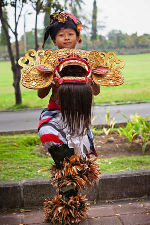 Bali, Indonesia - June 23, 2018: Dancer boy in ethnic costumes with traditional mask of Balinese good spirit Barong on hindu ceremony Ngelawang during temple festival. Editorial