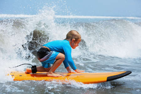 Happy baby boy - young surfer ride on surfboard with fun on sea waves. Active family lifestyle, kids outdoor water sport lessons and swimming activity in surf camp. Beach summer vacation with child.