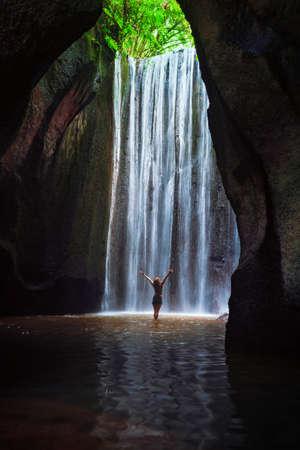 Femme debout dans la piscine souterraine de la grotte sous la chute d'eau douce de la cascade Tukad Cepung. Excursion d'une journée dans la nature, aventure d'activités de randonnée et divertissement dans un camp touristique familial en vacances d'été sur l'île de Bali