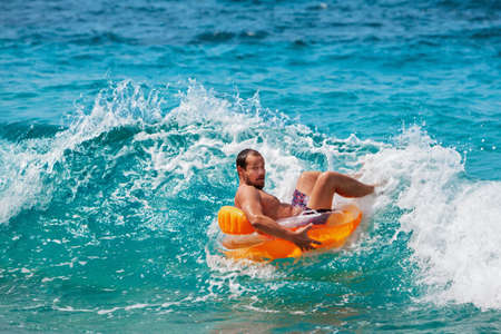 Excited bearded hipster in inflatable ring have fun in beach surf. Funny man riding on tubing in breaking sea waves. Family travel lifestyle, swimming activities. Summer vacation on tropical island.