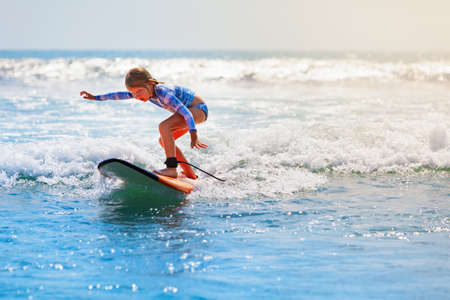 Happy baby girl - young surfer ride on surfboard with fun on sea waves. Active family lifestyle, kids outdoor water sport lessons and swimming activity in surf camp. Beach summer vacation with child. Foto de archivo
