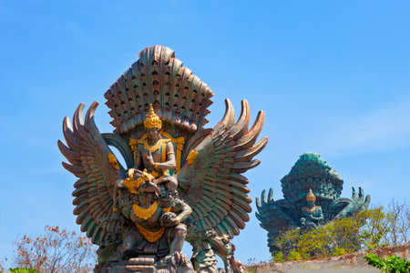 Landscape picture of old Garuda Wisnu Kencana GWK statues as  Bali landmark with blue sky as a background. Balinese traditional symbol of hindu religion. Popular travel destinations in Indonesia.