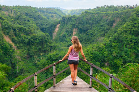 Family vacation lifestyle. Young woman stand on edge of overhanging bridge on high cliff. Happy girl looking at stunning tropical jungle view. Tukad Melangit is popular travel destination in Bali. 版權商用圖片 - 117181544