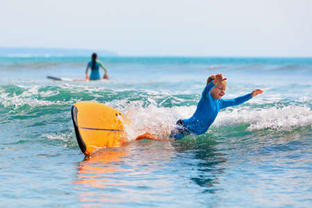 Happy boy - young surfer learning ride and fall from surfboard with fun. Active family lifestyle. Kids surf lessons, outdoor water sport activity in surfing camp. Beach summer vacation with child. Stock Photo