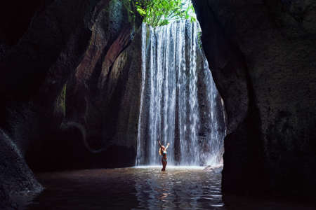 Woman stand in underground cave pool under falling fresh water of Tukad Cepung waterfall. Nature day tour, hiking activity adventure and fun at family tourist camp on summer vacation in Bali island