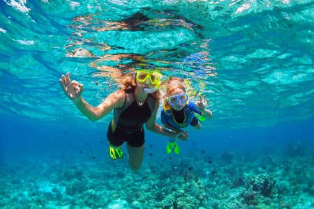 Glückliche Familie - Mutter, Kind in Schnorchelmaske tauchen unter Wasser mit tropischen Fischen im Korallenriff-Meerespool. Zeigen Sie mit den Händen Taucherzeichen OK. Reiselebensstil, Strandabenteuer im Sommerurlaub mit Kind.