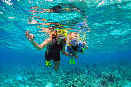 Happy family - mother, kid in snorkeling mask dive underwater with tropical fishes in coral reef sea pool. Show by hands divers sign OK. Travel lifestyle, beach adventure on summer holiday with child. Imagens - 117181699