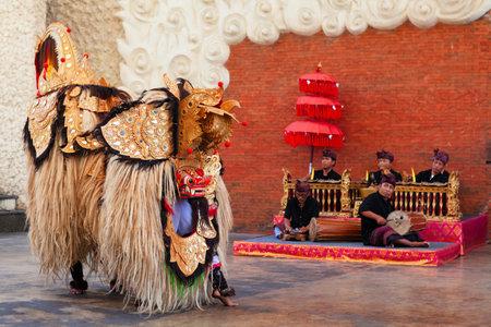 Bali, Indonesia - October 10, 2018: Men dancing traditional Keris (Kris) dance in mask and costume of balinese spirit Barong. Public show on open stage in Garuda Wisnu Kechana cultural park Editorial