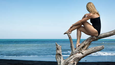 Girl with slim body in swimsuit sit and relax on old tree snag, posing on black sand sea beach. Young dreaming woman look at sea surf, wave. Solitude concept. Retreat leisure on summer family vacation