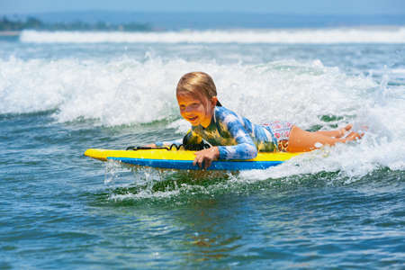Happy baby girl - young surfer ride on surfboard with fun on sea waves. Active family lifestyle, kids outdoor water sport lessons and swimming activity in surf camp. Beach summer vacation with child. 写真素材
