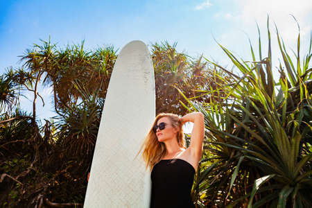 Surfer girl in black bikini with surfboard posing by palms on beach with sun. Young woman look at sea surf and waves. Active people in sport adventure camp, extreme activity on summer family vacation