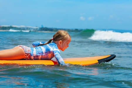 Happy baby girl - young surfer paddle on surfboard with fun on sea waves. Active family lifestyle, kids outdoor water sport lessons and swimming activity in surf camp. Beach summer vacation with child