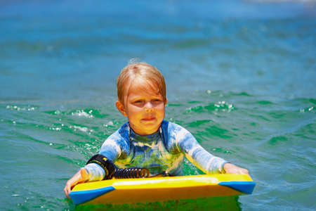 Happy baby girl - young surfer ride on surfboard with fun on sea waves. Active family lifestyle, kids outdoor water sport lessons and swimming activity in surf camp. Beach summer vacation with child. Stock Photo