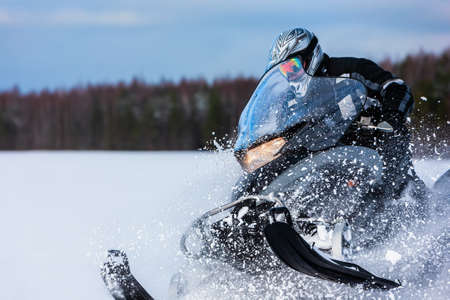 In deep snowdrift snowmobile rider driving fast. Riding with fun in white snow powder during backcountry tour. Extreme sport adventure, outdoor activity during winter holiday on ski mountain resort. 版權商用圖片