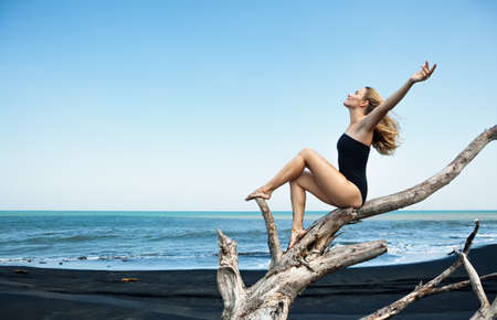Young  happy girl in swimsuit sitting on old tree snag rise hands high in air, posing on black sand sea beach. Travel lifestyle concept. Retreat leisure on summer family vacation in tropical island