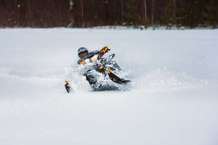 In deep snowdrift snowmobile rider make fast turn. Riding with fun in white snow powder during backcountry tour. Extreme sport adventure, outdoor activity during winter holiday on ski mountain resort.