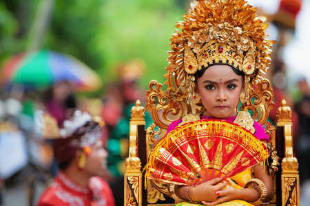 Denpasar, Bali island, Indonesia - June 23, 2018: Face portrait of beautiful young woman in traditional Balinese dance costume with golden headdress on street parade at art and culture festival. Editorial