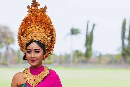 Denpasar, Bali island, Indonesia - June 23, 2018: Face portrait of beautiful young woman in traditional Balinese dance costume with golden headdress on street parade at art and culture festival. 에디토리얼
