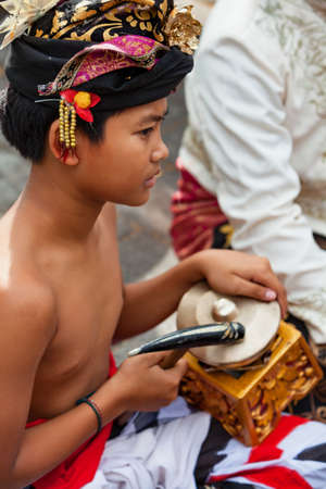 Denpasar, Bali island, Indonesia - June 23, 2018: Musician man in traditional dance costume playing brass gong ( part of Balinese orchestra Gamelan Kebyar) on street parade at art and culture festival