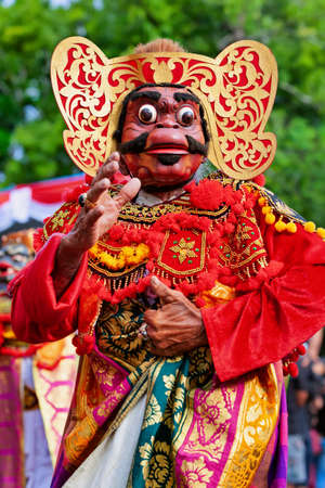 Dancer man in traditional Balinese costume, face mask Tari Wayang Topeng - character of Bali culture. Temple ritual dance at ceremony on religious holiday. Ethnic festivals, arts of Indonesian people Stock Photo