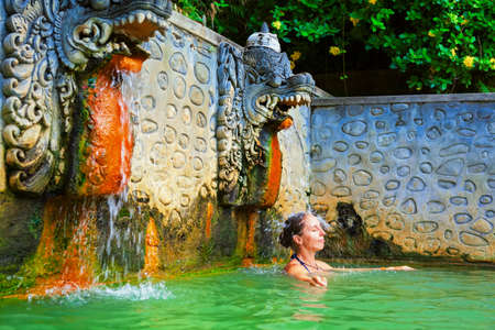 Young woman stand in thermal bath, relaxing under flowing water stream of shower in natural mineral hot spring Banjar. Day tour on family holidays. Popular travel destination, traditional spa in Bali
