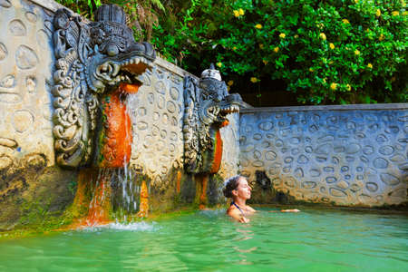 Young woman stand in thermal bath, relaxing under flowing water stream of shower in ancient Balinese hot spring. Day tour on family holidays. Popular travel destination, traditional spa in Bali Stock Photo